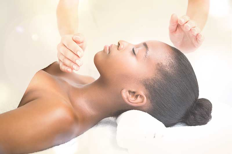 Person getting a body treatment with the Reiki technique
